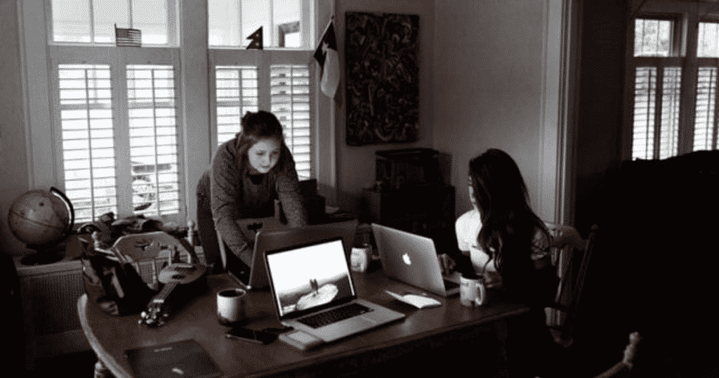 Women uing laptops on a brown wooden table-Benefits of blogging for small businesses